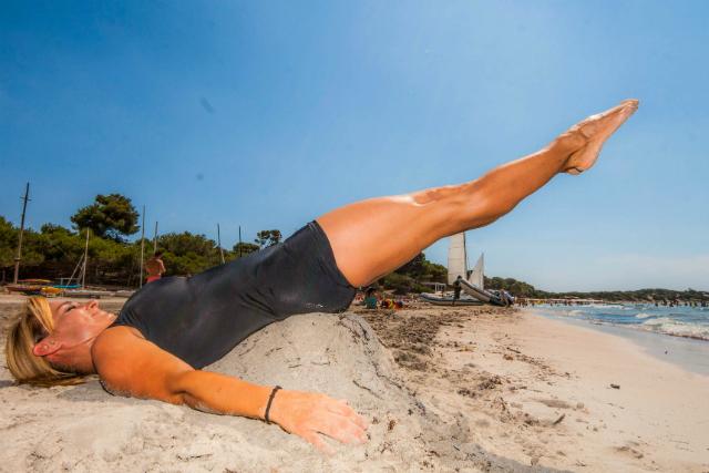 Ejercicio de Pilates de piernas y abdomen en la playa.